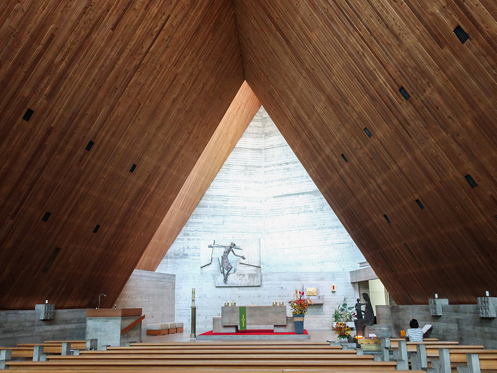 <p>The interior of the church has a clean simple feel thanks to the use of few materials such as concrete and larch wood. The chancel is set back and has a high roof allowing light to fall directly into the altar space. (image used with permission)</p>