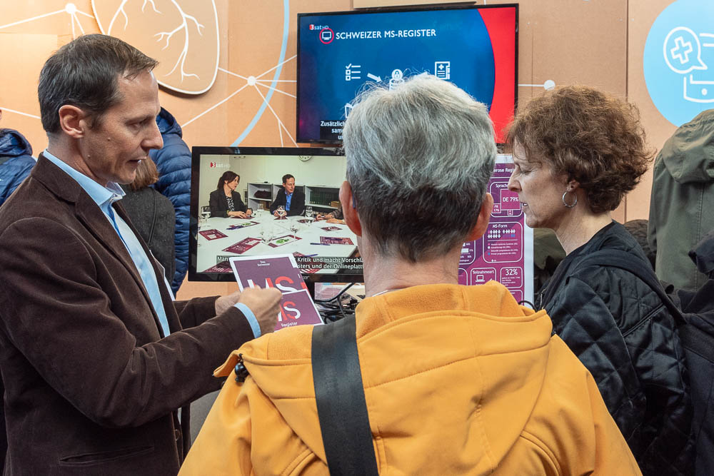 <p>Viktor von Wyl presents UZH's Swiss multiple sclerosis registry to visitors at Digital Day.</p> (Image: Thomas Poppenwimmer)